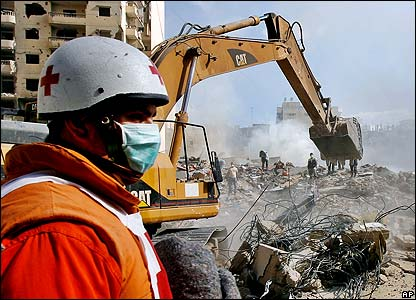 Red Cross worker stands in front of rubble being searched for victims in Beirut, after an Israeli strike on Sunday