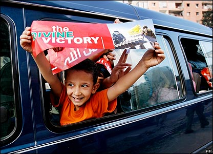 Boy in car holds up Hezbollah banner