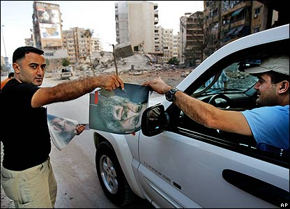 Hezbollah supporter hands out poster to motorist in Beirut
