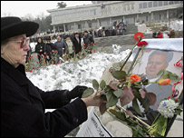 Woman lays roses in front of picture of Milosevic