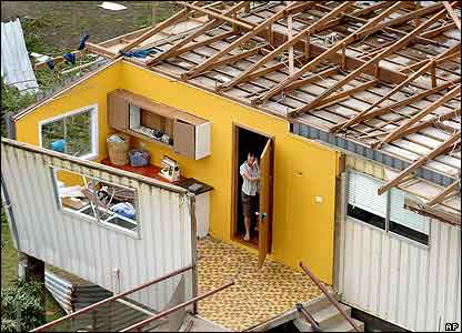 The roof of this woman's also house blew away in the storm. Here  makes a phone call from her ruined home in Innisfail in north-east Australia