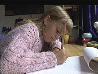 A girl writing on paper with a pen