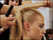 A hairdresser styling a model's hair