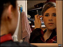 A girl looking in a mirror and putting on make-up.