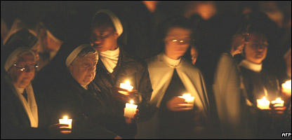Nuns hold candles as Pope Benedict XVI arrives for an Easter service in St. Peter's Basilica at the Vatican in Italy