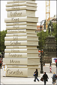Visitors look at a sculpture of piled-up books by German writers in Berlin.