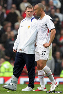 Wayne Rooney, with his strapped-up broken foot, talks with Mikael Silvestre.