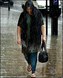 A woman gets drenched in rain in Leeds