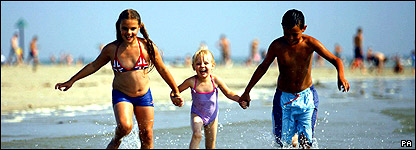 Three children splashing in the waves