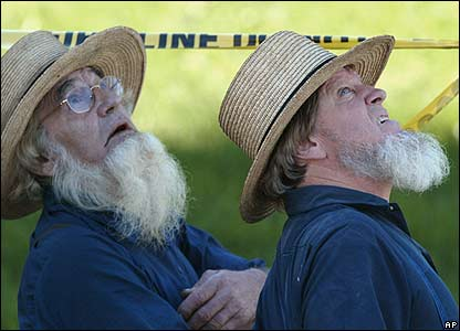 Amish people wait for news behind a police cordon