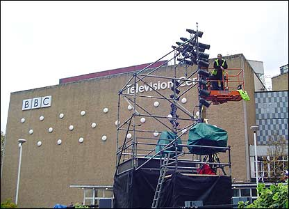 These men are up a crane trying to fix the lights so they light up the stage brilliantly