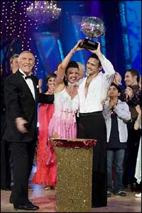They lift the trophy, surrounded by family and friends and the show's host, Bruce Forsyth