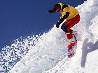 Snowboarder leaping off ledge of snow