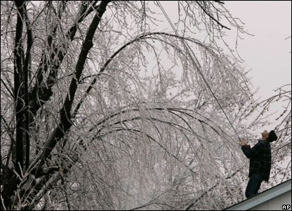 Tim Curry uses a rope to pull down icy branches hanging low over the roof of his sister's home  in St. Charles, Mo