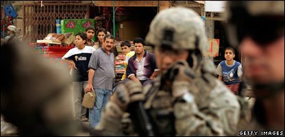 People watch as U.S. Army soldiers of the 82nd Airborne Division patrol through streets April 18, 2007 in Baghdad, Iraq