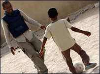 Lizo playing football with kids in Iraq. Picture by Cpl Wayne Beeching/Crown copyright
