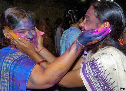 Women rubbing the coloured powders on each other