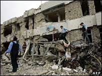 Iraqi police sift through the rubble of a bombed police station in Doura