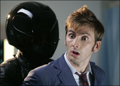 The Doctor being held by a character dressed in black.