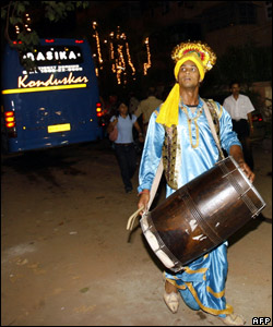 A folk dancer stands next to a bus carrying guests to the residence of Bollywood film actress Aishwarya Rai in Mumbai