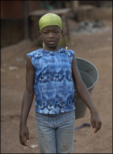 A young girl at the market. Many children have to work lots of hours to make money for their family.