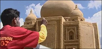 Artists working on his sand sculpture of the Taj Mahal