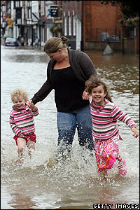 The floods have caused damage to thousands of homes, but these girls don't let it get them down. They enjoy a splash in the water, while holding carefully on to mum.