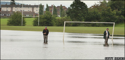 Two men fishing on a football pitch