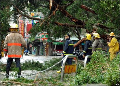 Firefighters look at some of the damage caused by the typhoon