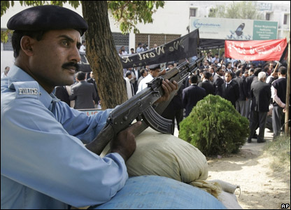 Police on duty while protestors march through the streets of Pakistan