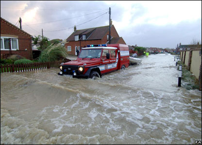 A fire and rescue vehicle makes its way through a flooded street at Walcott near Great Yarmouth