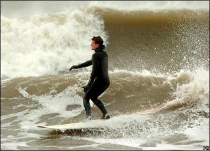 A surfer rides a wave in Gorleston-on-Sea