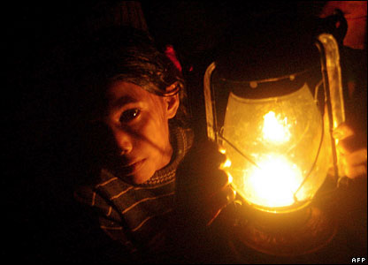 A Bangladeshi girl holds a lamp in a cyclone shelter near Mongla