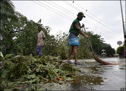 Man sweeping up leaves after the Cyclone