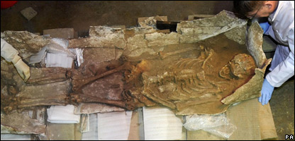 A 2,000 year old lead coffin and skeleton are examined