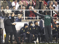 An Uefa official gestures to coach Arsene Wenger of Arsenal as he tries to watch the match from the side after he was sent off