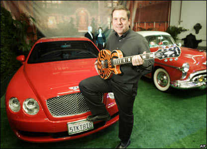 Auctioneer Darren Julien holds a signed guitar in front of Ozzy Osbourne's 2006 Bentley and Sharon Osbourne's 1950 Oldsmobile