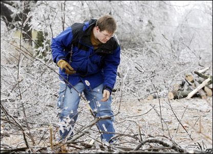 A man clearing fallen branches from outside his home