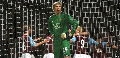 Manchester United's Tomasz Kuszczak stands dejected as West Ham United players celebrate Matthew Upson scoring their second goal