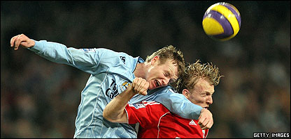 Manchester City's Richard Dunne (left) clashes with Liverpool's Dirk Kuyt