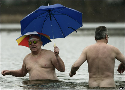 Two men in the water with an umbrella
