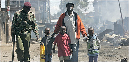 A policeman escorts a man and his children during one of the riots in Kenya