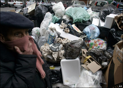 A man covering his nose as he walks past massive piles of rubbish