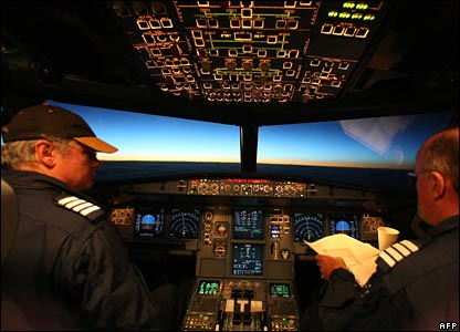 Pilots in the cockpit of the plane as it flies into the midnight sun.