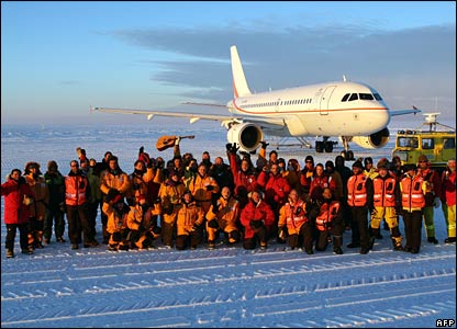 Passengers, scientists and ground crew pose in front of the plane