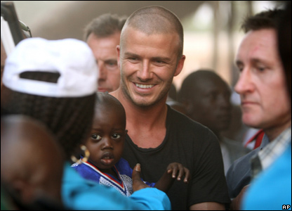 David Beckham talks with children and families, after taking part in a game of soccer