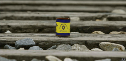 A memorial candle in a tin sits on the train tracks at a former concentration camp in Auschwitz, Poland