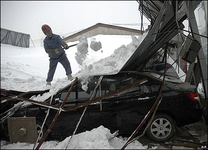 Worker shovels snow from collapsed car showroom