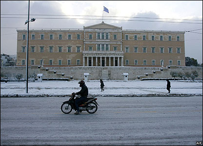 Many vehicles remained parked up because the weather conditions made driving too tricky. But this motorcyclist was determined to make his trip past the Greek Parliament.