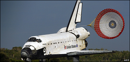 The space shuttle Atlantis with parachute